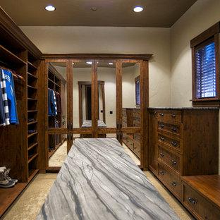 Foto di una cabina armadio unisex rustica con ante con riquadro incassato, ante in legno bruno, moquette e pavimento beige