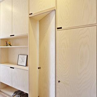 Foto di un armadio o armadio a muro unisex nordico con ante lisce, ante in legno chiaro e pavimento in legno massello medio