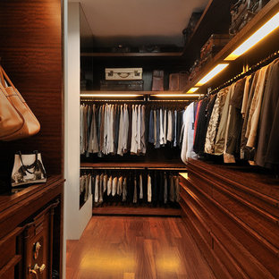 This is an example of a contemporary gender-neutral walk-in wardrobe in Singapore with dark wood cabinets and brown floor.
