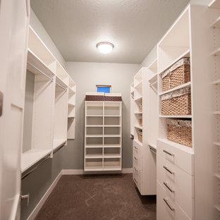 Cette image montre un dressing design de taille moyenne et neutre avec un placard à porte plane, des portes de placard blanches, moquette et un sol marron.