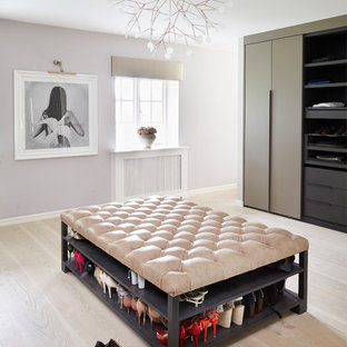 Example of a large trendy light wood floor and beige floor dressing room design in London with flat-panel cabinets