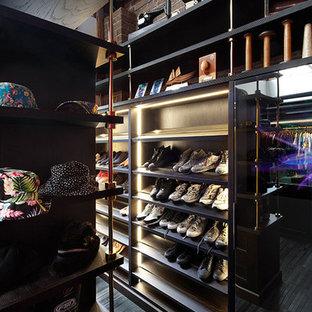 Immagine di un'ampia cabina armadio unisex boho chic con ante nere e pavimento in legno massello medio