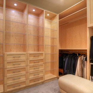 Large transitional gender-neutral dressing room in San Diego with shaker cabinets, light wood cabinets, carpet and beige floor.