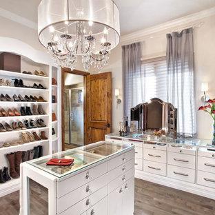 Ejemplo de vestidor de mujer, contemporáneo, grande, con armarios con paneles lisos, puertas de armario blancas y suelo de madera en tonos medios