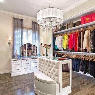 Réalisation d'un grand dressing room tradition pour une femme avec des portes de placard blanches, un sol en bois brun et un placard sans porte.