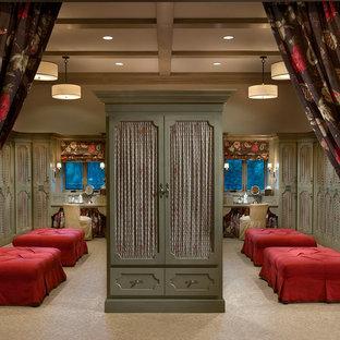 Réalisation d'un très grand dressing room chalet avec des portes de placards vertess et moquette.