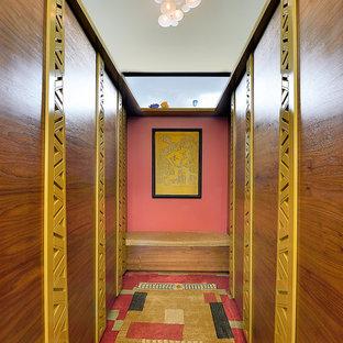 Ejemplo de armario vestidor unisex, ecléctico, de tamaño medio, con armarios con paneles lisos, puertas de armario de madera oscura, moqueta y suelo multicolor