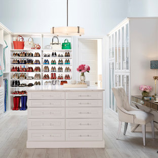 Elegant gender-neutral light wood floor walk-in closet photo in Dallas with white cabinets and raised-panel cabinets