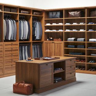 Diseño de armario vestidor de hombre, clásico renovado, con armarios estilo shaker, puertas de armario de madera oscura y suelo de cemento