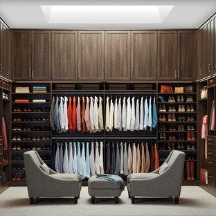 Modelo de vestidor unisex, clásico renovado, con armarios estilo shaker, puertas de armario de madera en tonos medios y moqueta