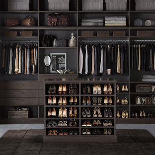 Contemporary gender-neutral walk-in wardrobe in Other with flat-panel cabinets, dark wood cabinets and concrete floors.