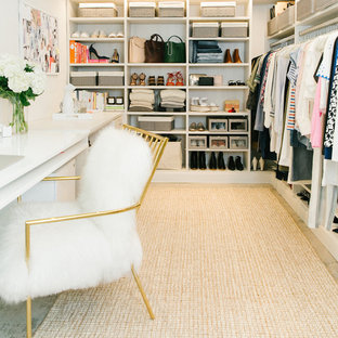 Inspiration for a large contemporary women's concrete floor walk-in closet remodel in Los Angeles with open cabinets and white cabinets