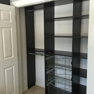 Foto di un armadio o armadio a muro unisex chic di medie dimensioni con moquette, nessun'anta e ante nere