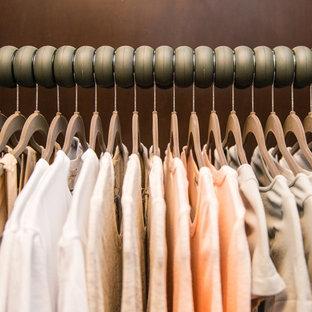 Cette image montre un petit dressing minimaliste pour une femme avec un placard à porte plane et des portes de placard en bois sombre.