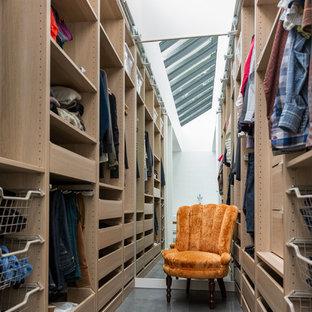 Ispirazione per una cabina armadio unisex minimal con nessun'anta e pavimento in cemento
