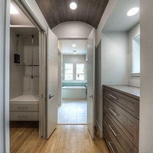 Foto de armario vestidor unisex, actual, grande, con armarios estilo shaker, puertas de armario con efecto envejecido y suelo de madera clara
