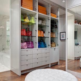 Idee per una cabina armadio design con ante grigie e pavimento in legno massello medio
