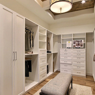 Expansive country gender-neutral walk-in wardrobe in Portland with recessed-panel cabinets, white cabinets, light hardwood floors and brown floor.