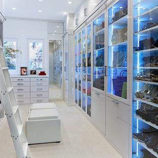 Ejemplo de vestidor unisex, actual, extra grande, con puertas de armario blancas, armarios tipo vitrina, moqueta y suelo beige