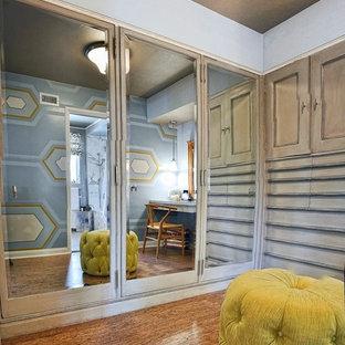 На фото: маленькая парадная гардеробная унисекс в классическом стиле с фасадами с утопленной филенкой, искусственно-состаренными фасадами и пробковым полом