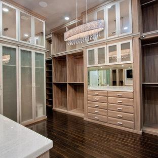 Ispirazione per un'ampia cabina armadio per donna chic con ante con bugna sagomata, ante in legno bruno e parquet scuro