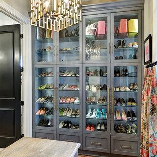 Immagine di una cabina armadio per donna classica con ante di vetro e ante grigie
