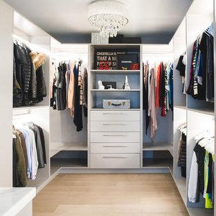 Idee per un grande spazio per vestirsi unisex design con nessun'anta, ante bianche, parquet chiaro e pavimento marrone