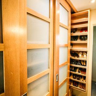 Immagine di una cabina armadio unisex tradizionale di medie dimensioni con ante di vetro, ante in legno scuro, pavimento in cemento e pavimento marrone