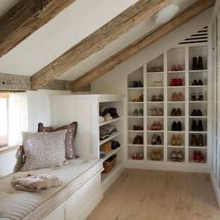 Inspiration for a mid-sized country gender-neutral walk-in wardrobe in Boston with open cabinets, white cabinets, light hardwood floors and brown floor.