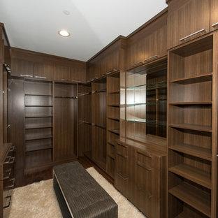 Diseño de armario vestidor unisex, retro, con armarios con paneles lisos, puertas de armario de madera oscura, suelo de madera en tonos medios y suelo marrón