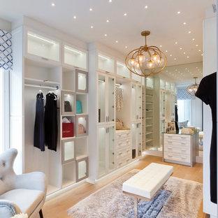 Exemple d'un très grand dressing chic pour une femme avec des portes de placard blanches, un sol en bois clair, un placard sans porte et un sol beige.