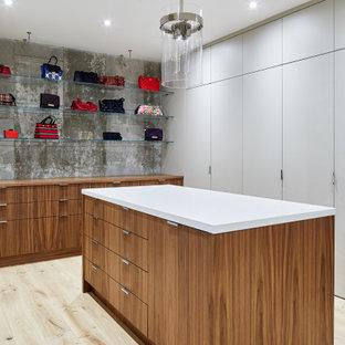 Réalisation d'un très grand dressing design neutre avec un placard à porte plane, des portes de placard en bois brun, un sol en contreplaqué et un sol beige.