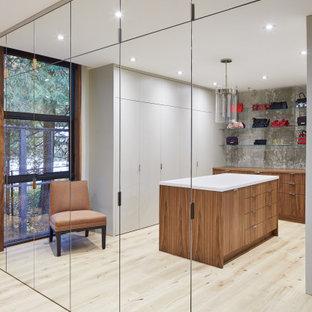 Ejemplo de armario vestidor unisex, actual, extra grande, con armarios con paneles lisos, puertas de armario de madera oscura, suelo de contrachapado y suelo beige