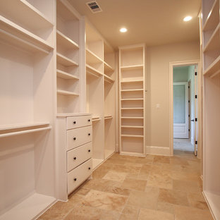 Large contemporary gender neutral walk-in wardrobe in Houston with flat-panel cabinets, white cabinets, travertine flooring and beige floors.