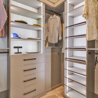 Diseño de armario vestidor de hombre, de estilo americano, grande, con armarios con paneles lisos, puertas de armario grises, moqueta y suelo beige