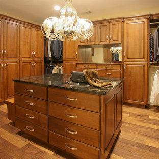 Imagen de armario vestidor unisex, bohemio, grande, con suelo de madera en tonos medios, armarios con paneles con relieve, puertas de armario de madera oscura y suelo marrón