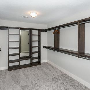Diseño de armario vestidor unisex, de estilo americano, grande, con puertas de armario de madera en tonos medios y moqueta