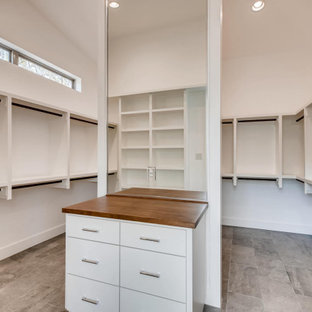 Cette image montre un grand dressing minimaliste neutre avec un sol en carrelage de céramique, un sol gris et un plafond en lambris de bois.