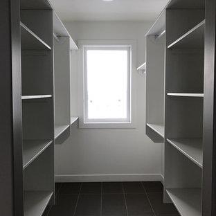 Ejemplo de armario vestidor unisex, de estilo americano, grande, con armarios abiertos, puertas de armario blancas y suelo de baldosas de porcelana
