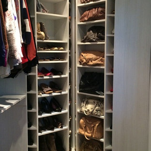 Photo of a large modern women's walk-in wardrobe in Miami with white cabinets.