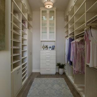 Modelo de armario vestidor de mujer, clásico renovado, de tamaño medio, con armarios con paneles lisos, puertas de armario de madera clara, suelo de madera oscura y suelo marrón