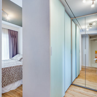 Ispirazione per una piccola cabina armadio unisex design con ante di vetro e pavimento in compensato
