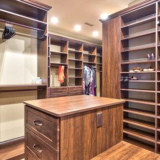 Modelo de armario vestidor unisex, rústico, grande, con armarios con paneles empotrados, puertas de armario marrones y suelo de madera en tonos medios