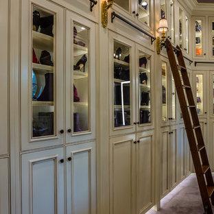 Imagen de armario vestidor de mujer, mediterráneo, con armarios con rebordes decorativos, puertas de armario de madera clara, moqueta y suelo violeta