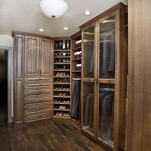 Idee per una cabina armadio unisex chic di medie dimensioni con ante con bugna sagomata, ante in legno scuro e parquet scuro
