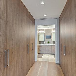 Ejemplo de vestidor unisex, clásico renovado, pequeño, con armarios con paneles lisos, puertas de armario marrones y suelo de madera clara