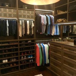 Diseño de armario vestidor de hombre, clásico, grande, con armarios con paneles con relieve, puertas de armario de madera en tonos medios, suelo de madera oscura y suelo marrón