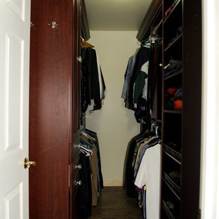Photo of a mid-sized traditional gender-neutral walk-in wardrobe in Philadelphia with raised-panel cabinets and brown cabinets.