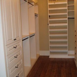 Modelo de armario vestidor de mujer, tradicional, grande, con armarios con paneles con relieve, puertas de armario blancas y suelo de madera en tonos medios