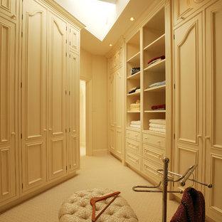 Diseño de vestidor tradicional con armarios con paneles empotrados y puertas de armario beige